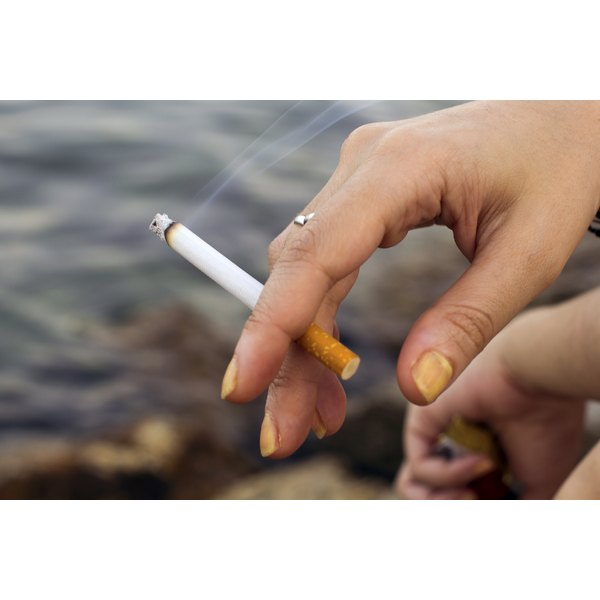 A woman holds a lit cigarette.