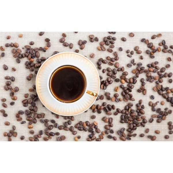 An overhead view of a cup of coffee on a table with coffee beans.