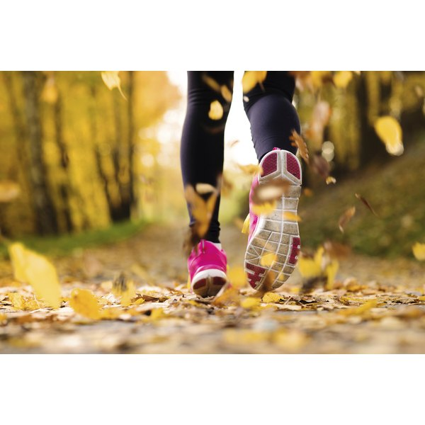 Woman jogging on a leaf-covered path