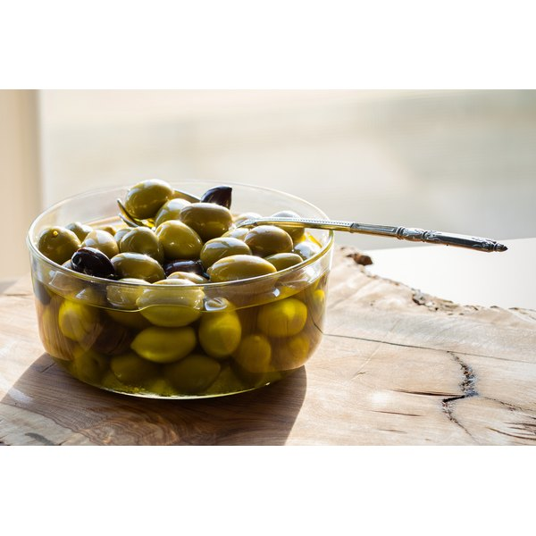 A bowl of marinated olives on a table.