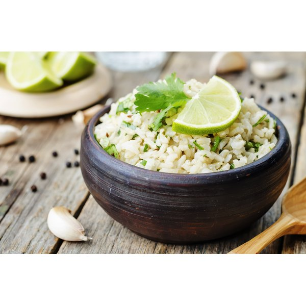 A bowl of brown rice with garlic, cilantro and lime.