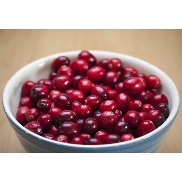 A bowl of fresh cranberries on a wooden table.