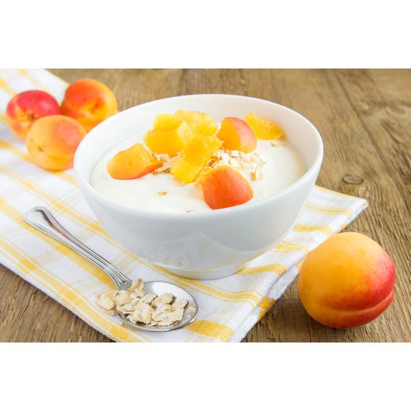 A large bowl of yogurt with fruit on top.