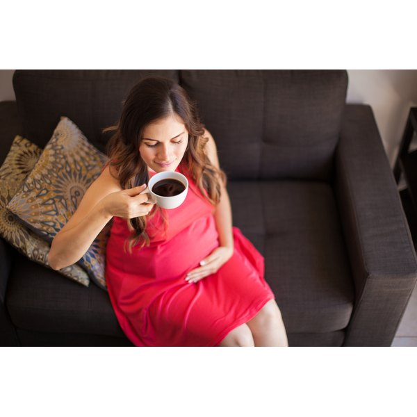 A pregnant woman is drinking a cup of coffee.