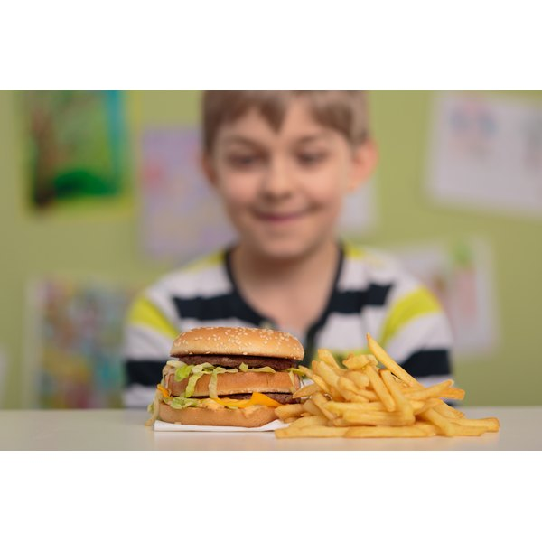 A boy smiling at a fast food burger and fries.