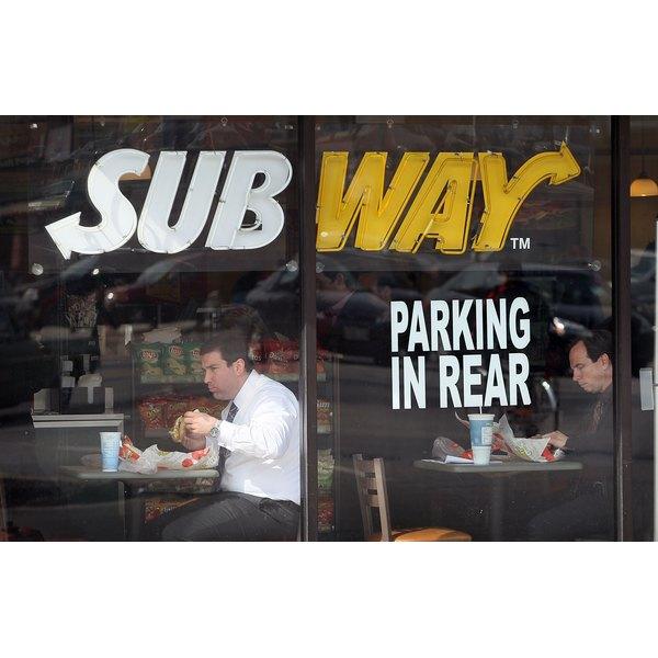 A man eating a sandwich inside of a Subway restaurant.