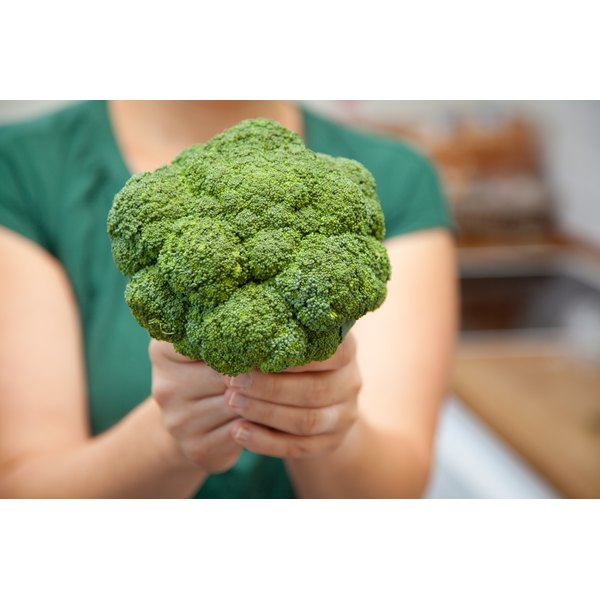 A woman holding a head of broccoli.