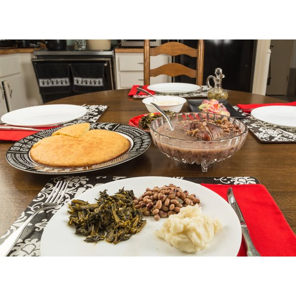 Southern-style collard greens on a plate with pinto beans, mashed potatoes and cornbread.