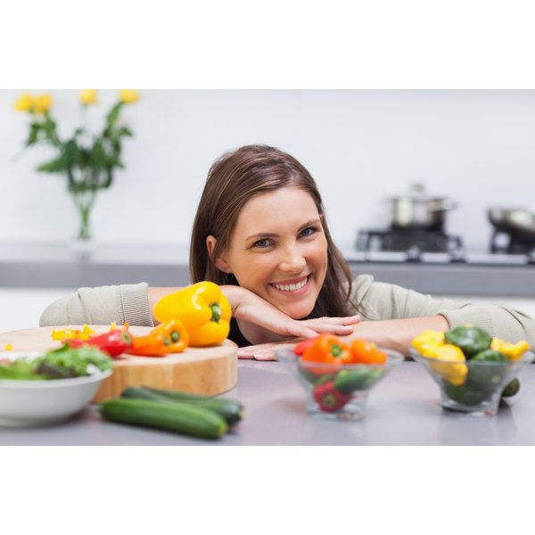 woman smiling behind bell peppers