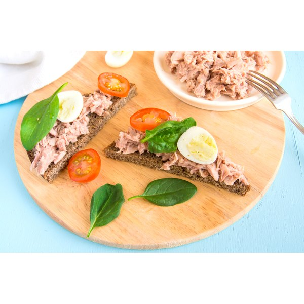 An open face tuna fish sandwich with tomato and egg.
