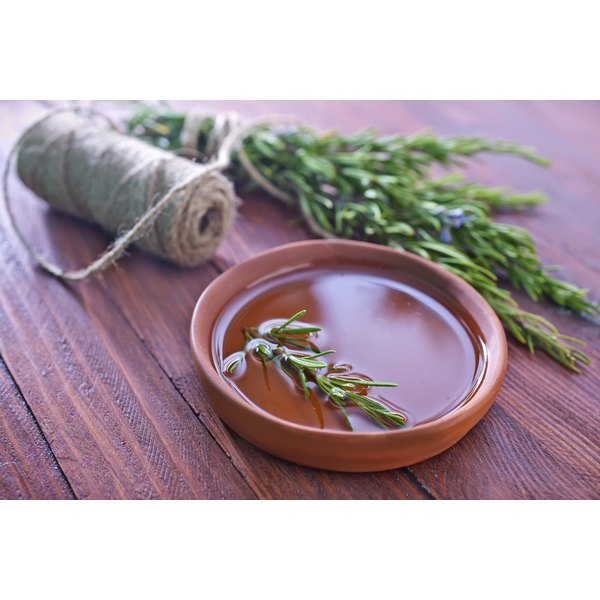 A ceramic dish of rosemary infused oil on a table with a bundle of fresh rosemary.