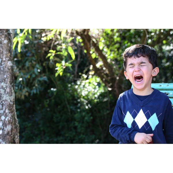 Child having tantrum in outdoor setting.