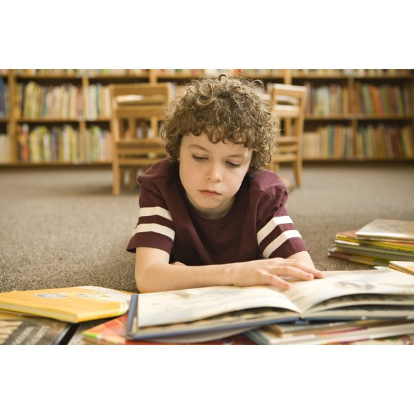 A boy reads a book at a desk in the library.