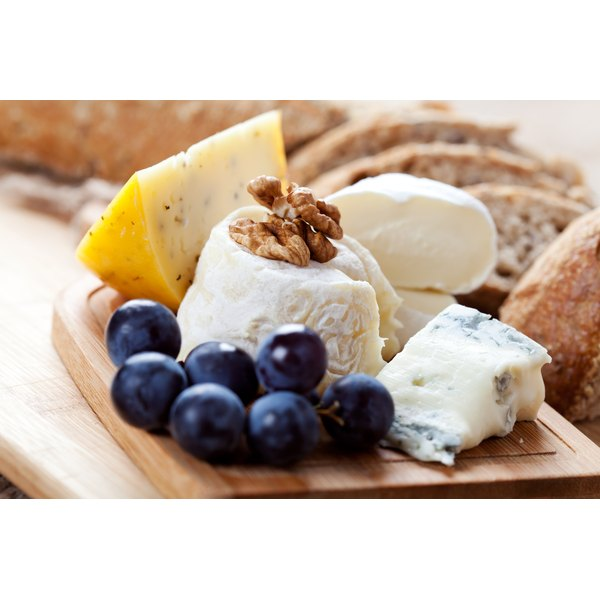 An assortment of cheeses and grapes on a cutting board.