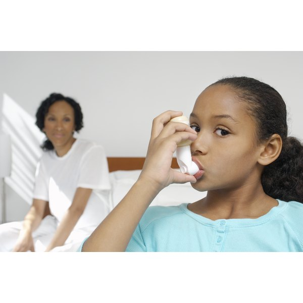 A young girl is using an inhaler.