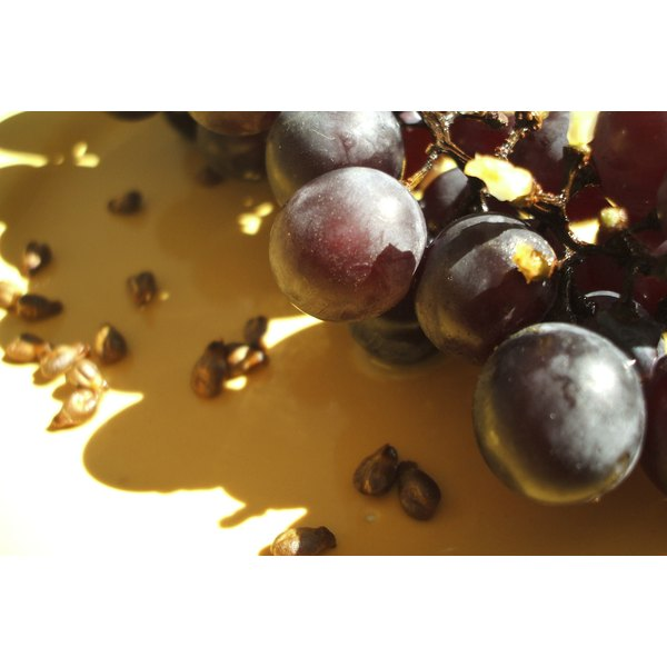Grape seeds and purple grapes on a table.
