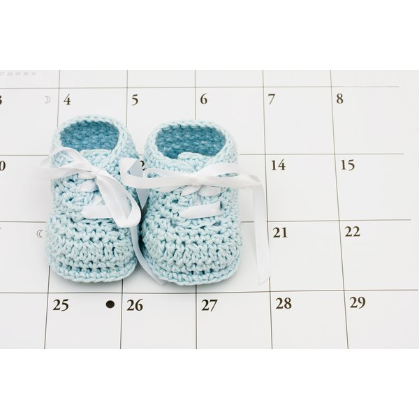 A pair of baby booties on a calendar.