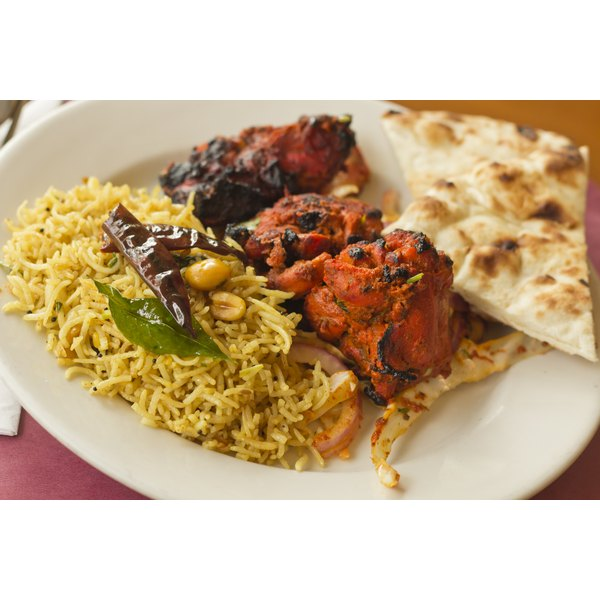 An Indian dish of tandoori chicken with rice and bread.