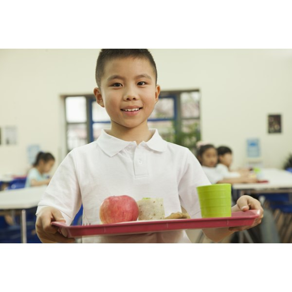 A boy carrying a healthy school lunch to a table in the cafeteria.