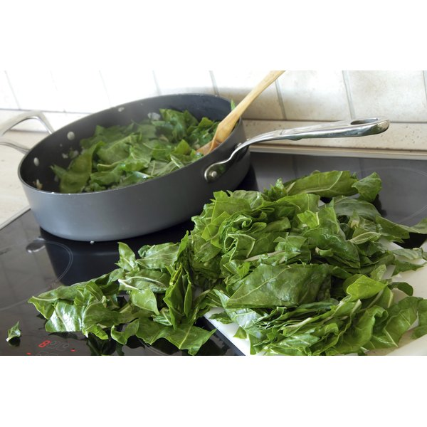 spinach leaves being cooked on stovetop