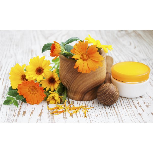 Calendula flowers in a mortar and pestle and a jar of salve.