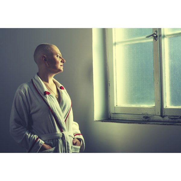 A cancer patient in a robe with shaved head stares out of the window in a hospital.