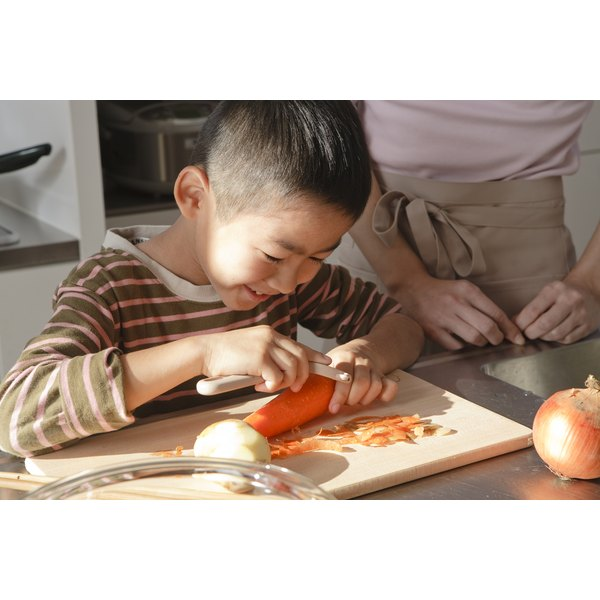 A young biy helps his mother in the kitchen by peeling a carrot.