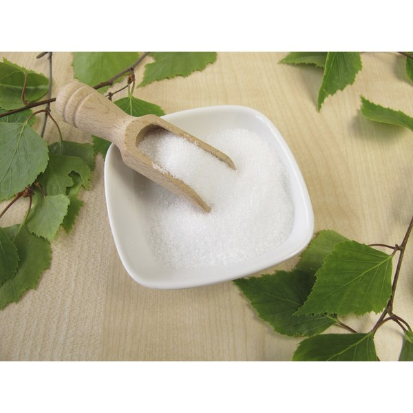 Xylitol in a bowl with a wooden scoop surrounded by birch leaves.