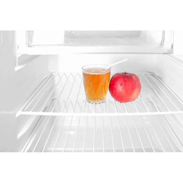A glass of apple juice and an apple sit on a shelf in the fridge.