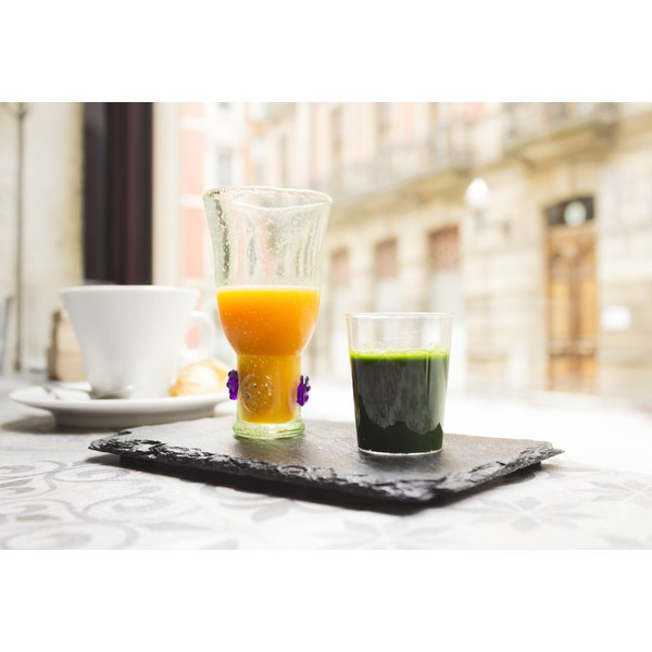 A shot of fresh wheatgrass on a table with other beverages.