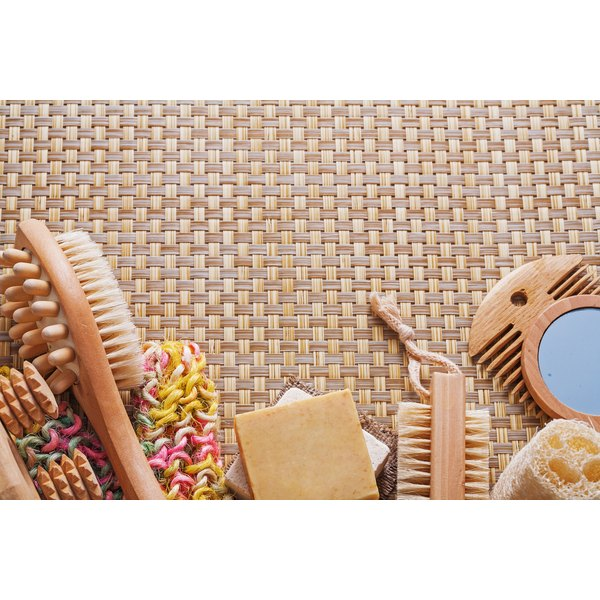 Bathroom items including a dry brush and a loofah sit on a mat in a spa setting.