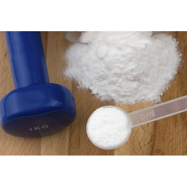 A spoonful and a mound of carnitine powder sit on a wooden table next to a handweight.