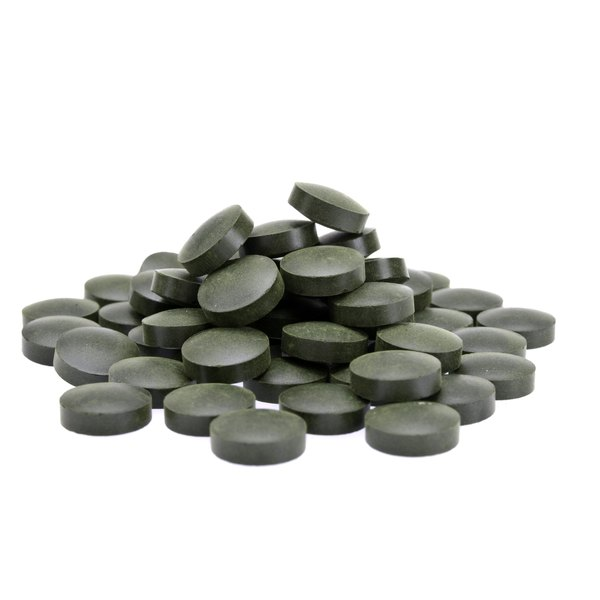 Spirulina pills sit on a white counter.