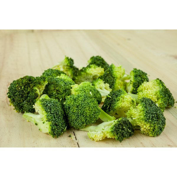 Steamed broccoli on a board.