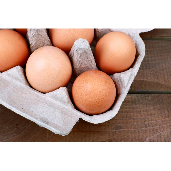 A close-up of a carton of eggs on a wooden table.