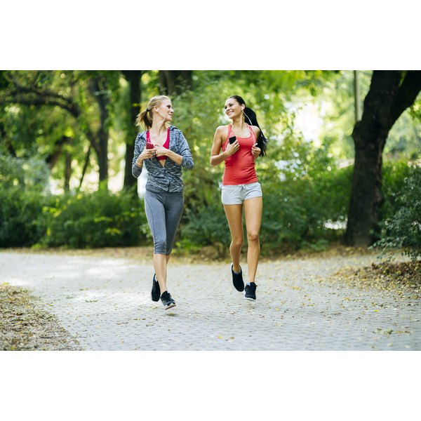 Two slim woman are jogging outside.