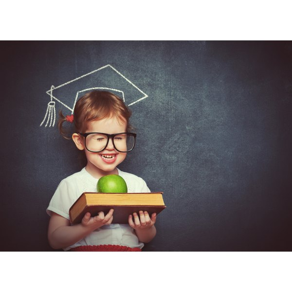 A young girl stands before a chalkboard where she is posing as if wearing a mortarboard hat, holding a book with a green apple atop it.