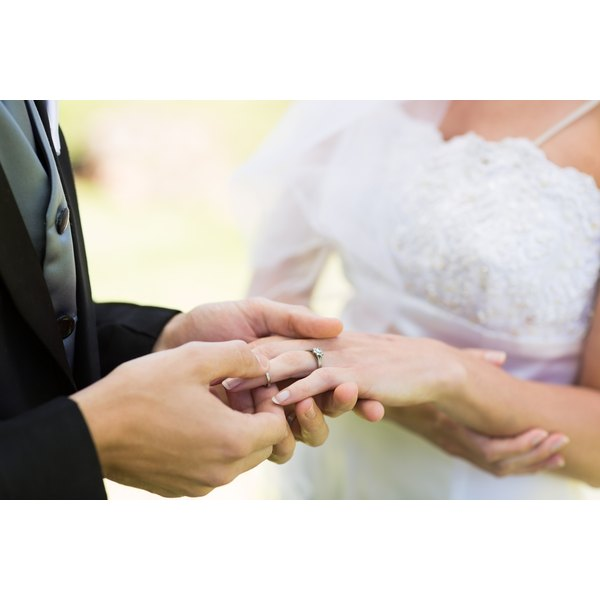 A close-up of a groom placing a wedding ring on a bride's finger.