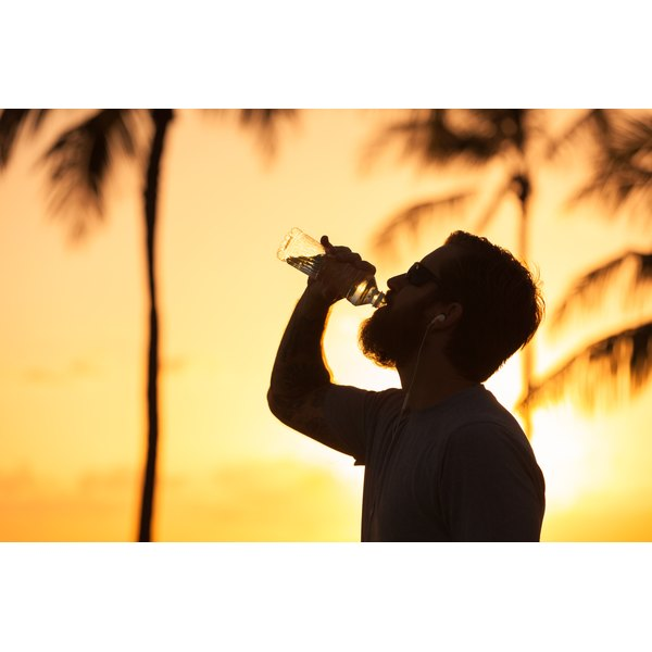 A bearded man gulps down a sports drink in the sunset with palm trees behind.
