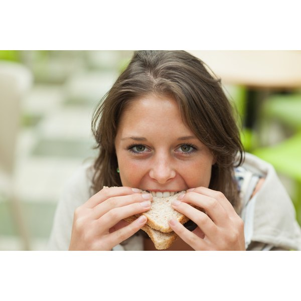 A close-up of a young woman eating a sandwich.