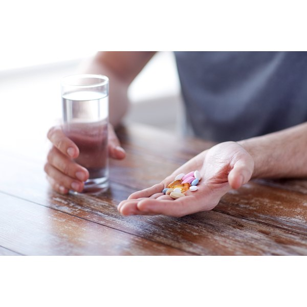 A man is holding vitamins in his hand, including a fish oil pill.