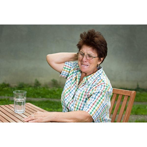 A woman sitting out doors on a picnic table grabs her neck as if in pain.