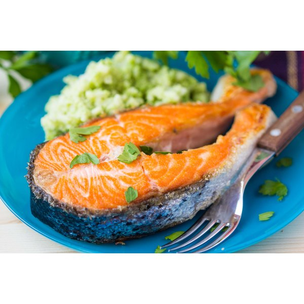A piece of salmon steak with risotto on a plate.