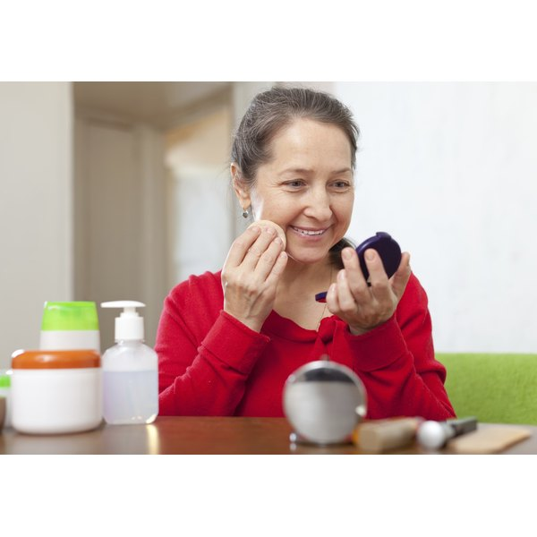 An older woman applying makeup while looking in a hand mirror.