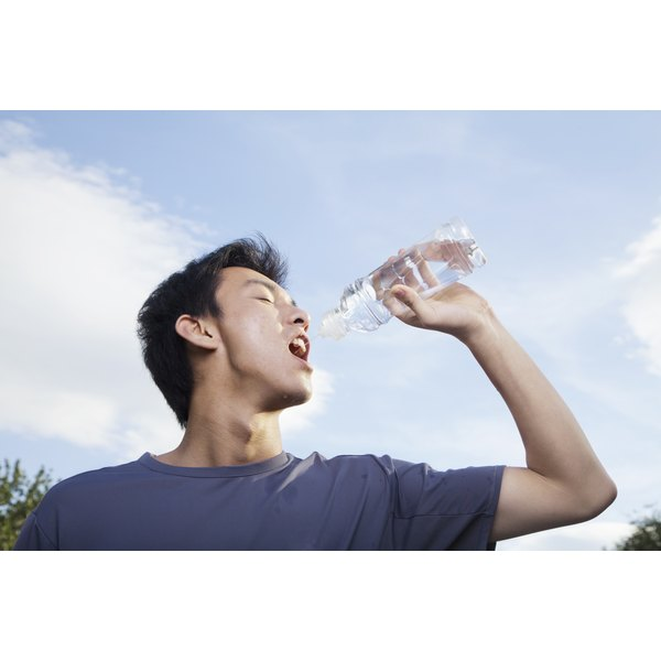 Young man holding up a water bottle to his mouth.