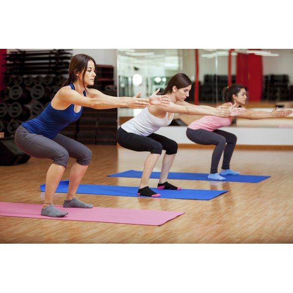 Three women do squats in a class at the gym.