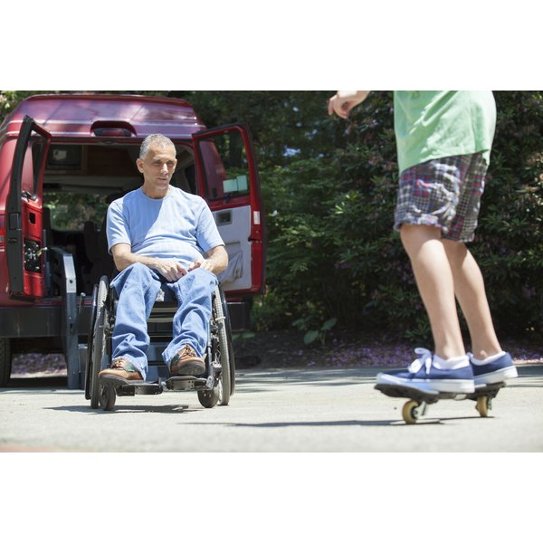 A father in his wheelchair watches his young son on a skateboard.