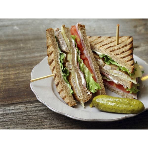 A large club sandwich on a small plate.