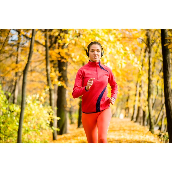A woman is jogging in a forest.