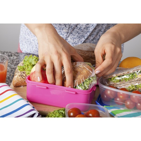 A woman packing lunches into plastic food containers.